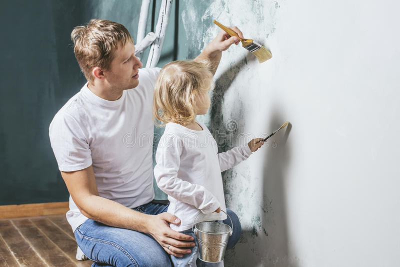 Famille, fille heureuse avec le papa faisant la réparation à la maison, murs de peinture, photographie stock libre de droits