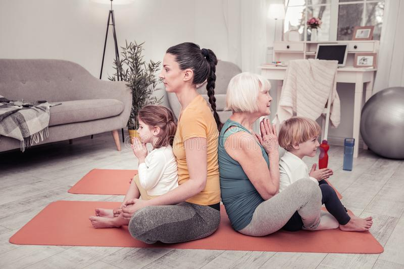 Famille folâtre et active faisant le yoga de matin ensemble image libre de droits