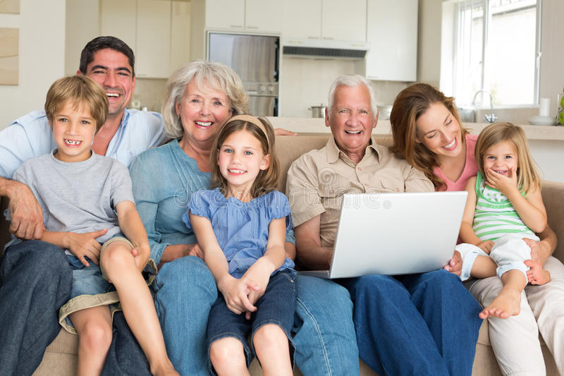 Famille gaie avec l'ordinateur portable dans le salon photographie stock libre de droits