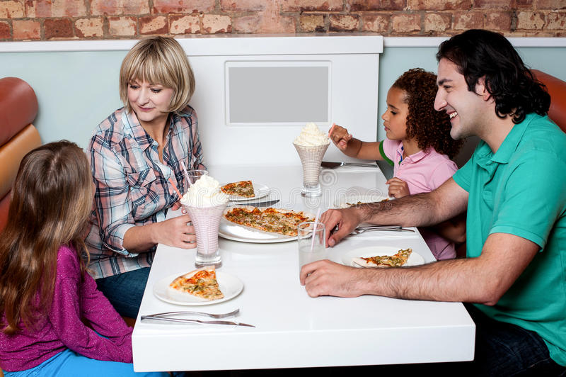 Famille gaie du petit déjeuner quatre appréciant image stock