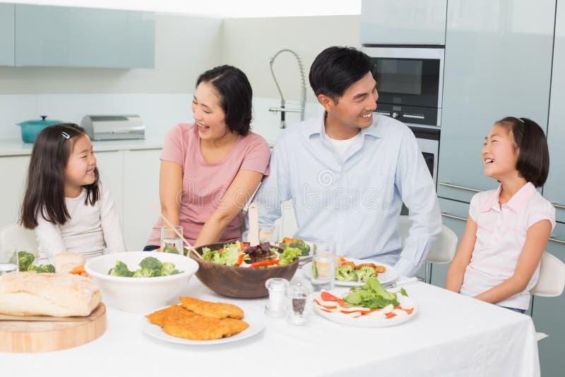 Famille gaie du repas quatre sain appréciant dans la cuisine images libres de droits