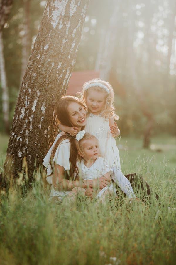 Famille gaie en parc, maman et leur belle fille deux ? reposer sur l'herbe tandis qu'ils regardent la cam?ra photos libres de droits