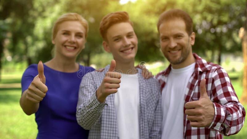 Famille gaie souriant montrant des pouces-, prêts lucratifs, crédits pour l'étude photo stock