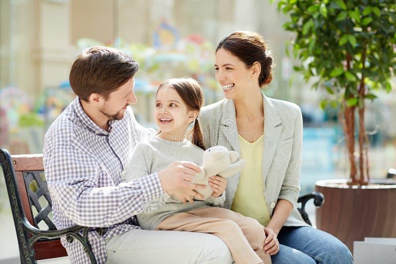 Famille gaie sur le banc dans le centre commercial image stock