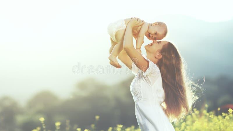 Famille heureuse à l'extérieur la mère jette le bébé, rire et le playi image libre de droits