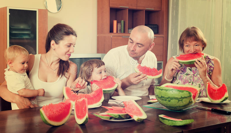 Famille heureuse ainsi que la pastèque au-dessus de la table de salle à manger photographie stock