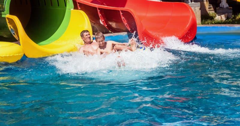 Famille heureuse appréciant la glissière de parc aquatique photos stock