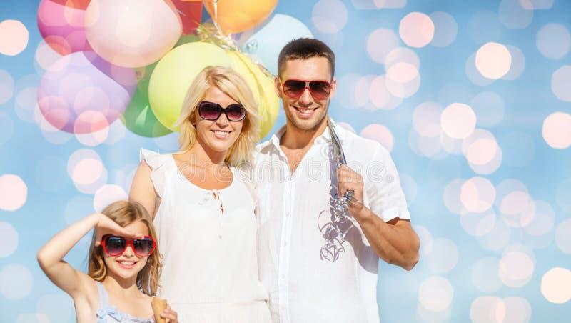 Famille heureuse avec des ballons au-dessus des lumières bleues photo libre de droits