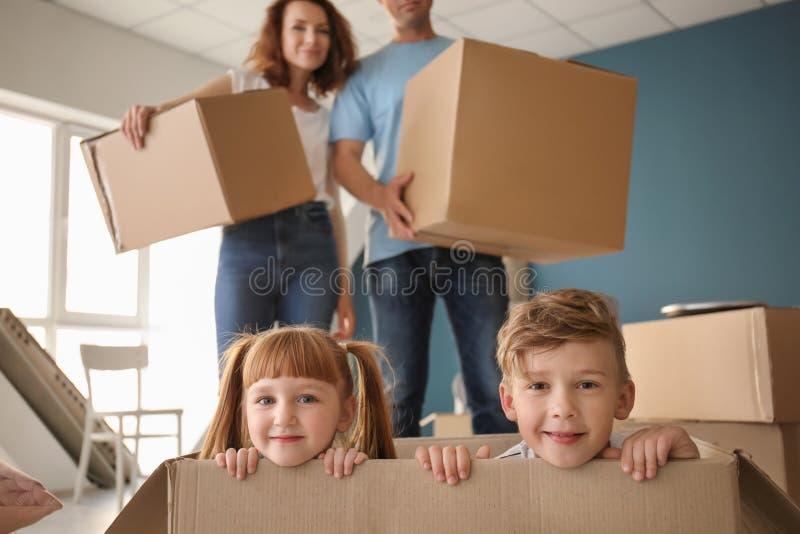 Famille heureuse avec des boîtes en carton à l'intérieur Entr?e dans la nouvelle maison images libres de droits