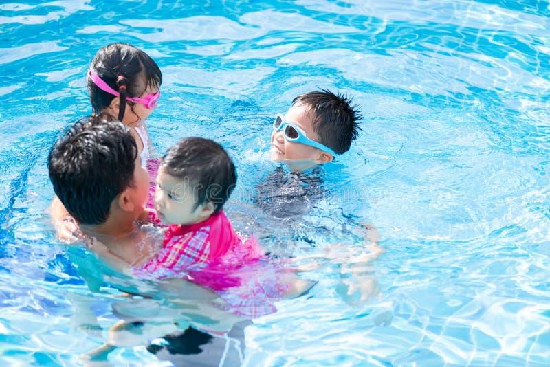 Famille heureuse avec des enfants ayant l'amusement dans la piscine photo stock