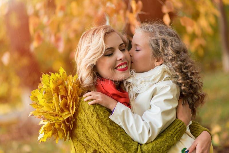 Famille heureuse avec des enfants sur la feuille orange d'automne extérieure photo stock