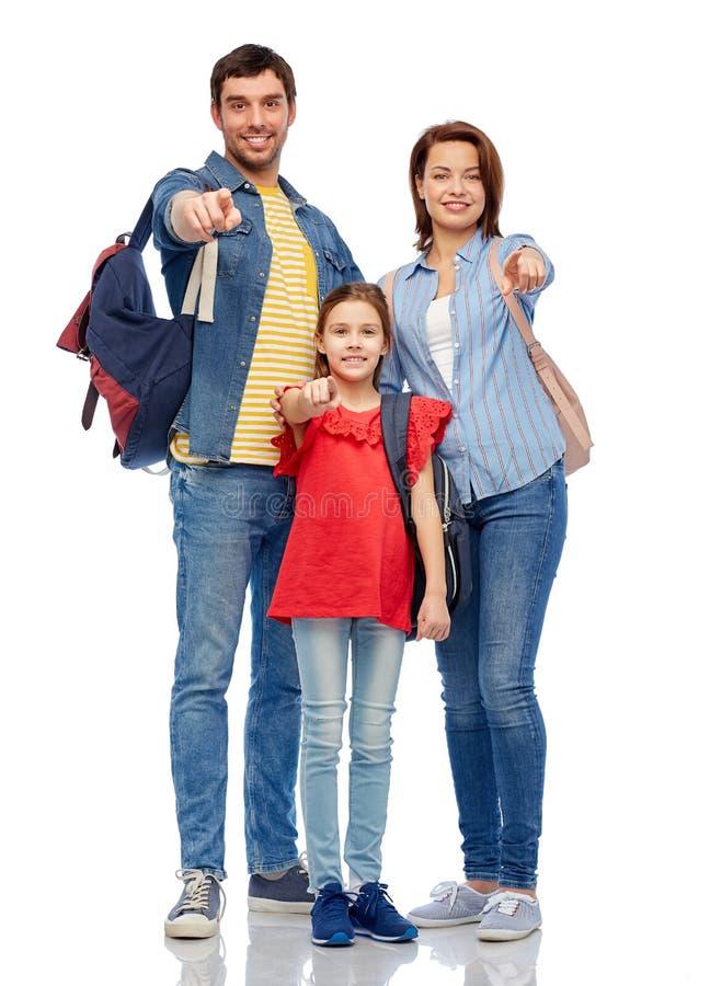 Famille heureuse avec des sacs à dos indiquant le doigt vous images libres de droits