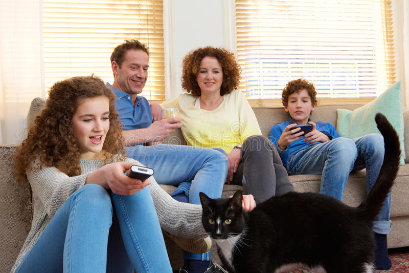 Famille heureuse avec l'animal familier de maison détendant à la maison images stock