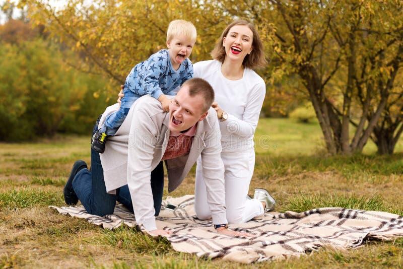 Famille heureuse avec l'enfant ayant l'amusement dans le parc d'automne se reposant sur un plaid images libres de droits