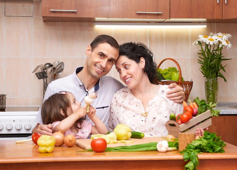 Famille heureuse avec l'enfant dans l'intérieur à la maison de cuisine avec des fruits frais et des légumes, femme enceinte, conc image stock