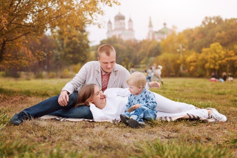Famille heureuse avec l'enfant en parc d'automne se reposant sur un plaid photos stock