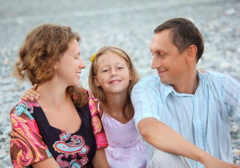 Famille heureuse avec la fille s'asseyant sur la plage pierreuse images libres de droits