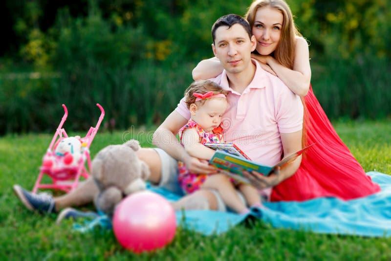 Famille heureuse avec la petite fille s'asseyant en parc sur la couverture photos stock
