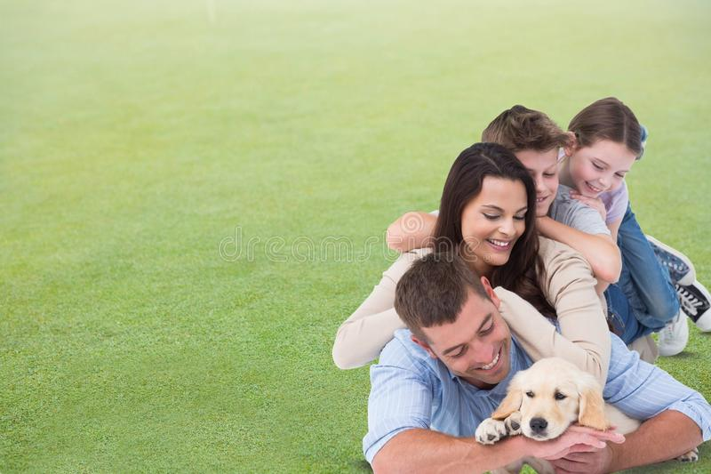 Famille heureuse avec le chien se trouvant sur l'herbe photo stock