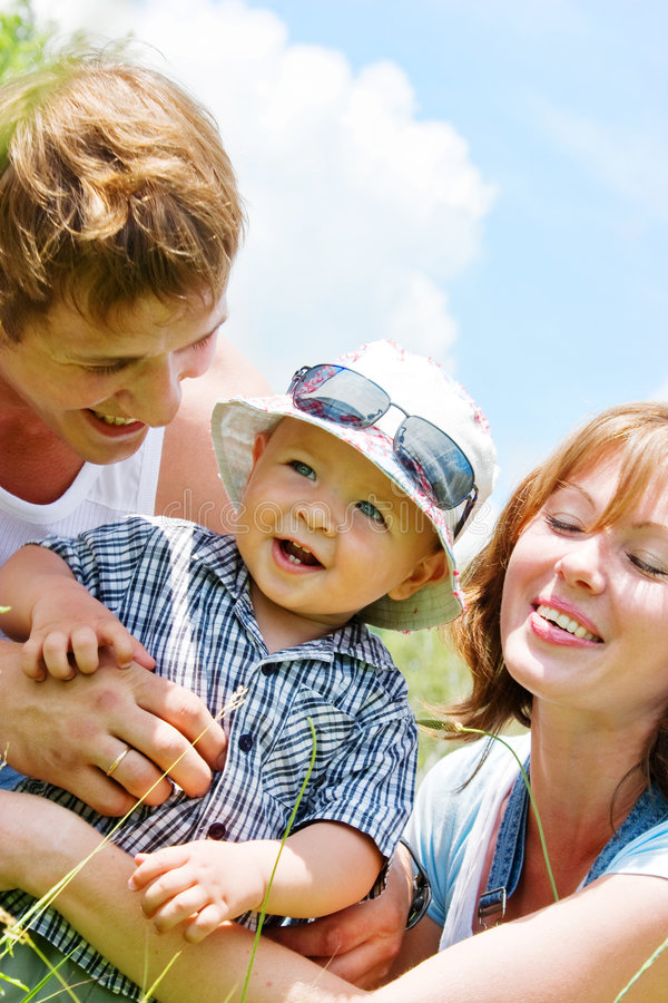 Famille heureuse avec le fils au-dessus du fond de ciel bleu photo libre de droits