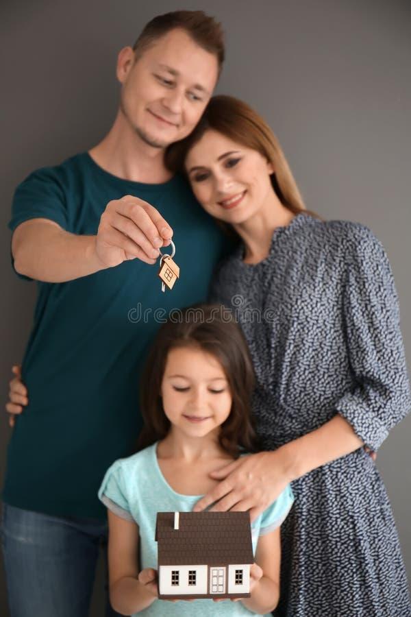 Famille heureuse avec le modèle de maison et la clé de leur nouvelle maison sur le fond gris photos stock