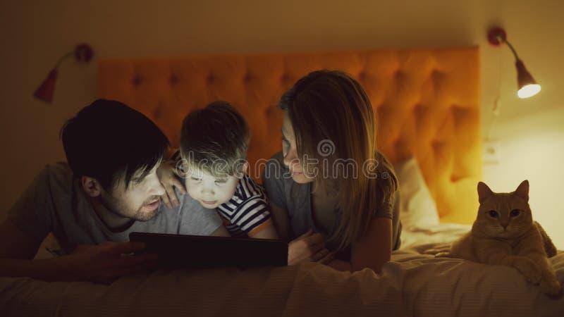 Famille heureuse avec le petit fils et le chat drôle se situant dans le lit à la maison et à l'aide de la tablette pour le film d image libre de droits