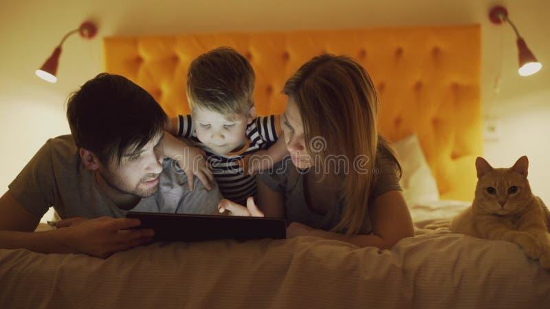 Famille heureuse avec le petit fils et le chat drôle se situant dans le lit à la maison et à l'aide de la tablette pour jouer le  image stock