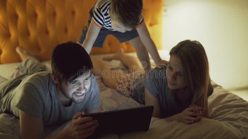 Famille heureuse avec le petit fils se trouvant dans le lit à la maison et le media social surfant sur la tablette devant le somm photographie stock