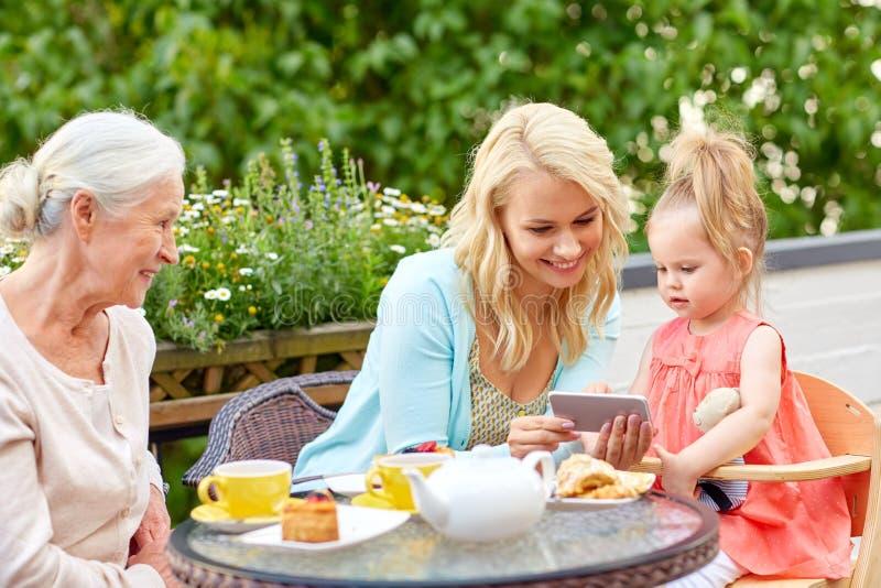 Famille heureuse avec le smartphone à la terrasse de café photo stock
