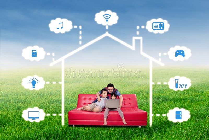 Famille heureuse avec le système futé de technologie de maison photos stock