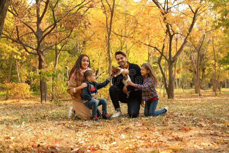 Famille heureuse avec les enfants et le chien en parc photos stock