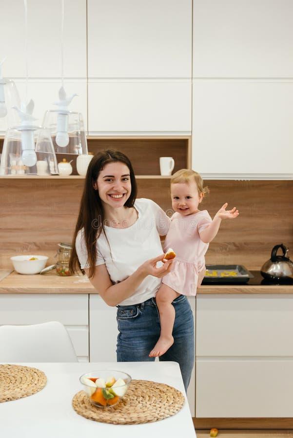 Famille heureuse avec peu de fille sur la cuisine ? la maison avant de prendre le petit d?jeuner, fruits frais photo libre de droits