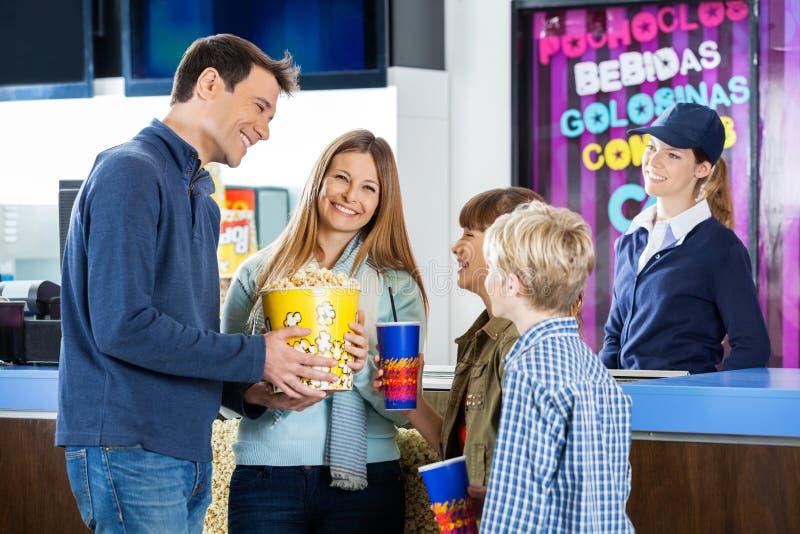 Famille heureuse ayant des casse-croûte à la concession de cinéma photos libres de droits