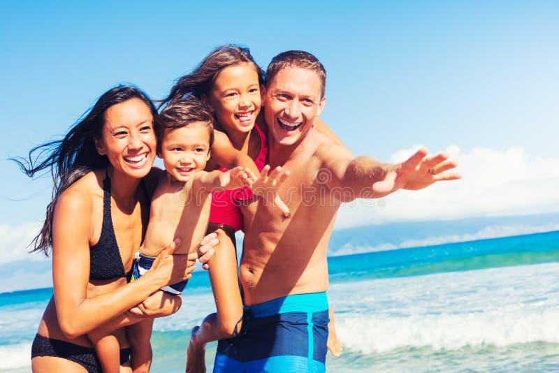 Famille heureuse ayant l'amusement à la plage photographie stock libre de droits