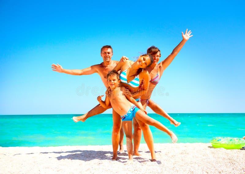 Famille heureuse ayant l'amusement à la plage images stock