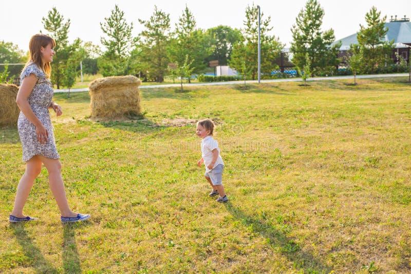 Famille heureuse ayant l'amusement bébé garçon et sa mère jouant dehors photo libre de droits