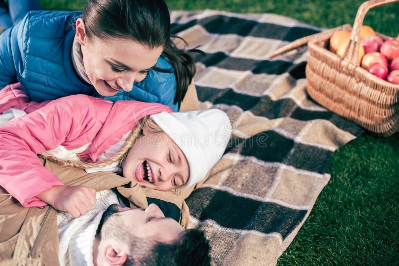 Famille heureuse ayant l'amusement dans le parc photos stock