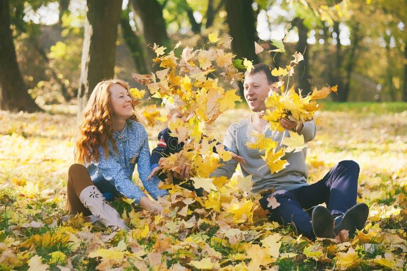 Famille heureuse ayant l'amusement dans le parc urbain d'automne images libres de droits