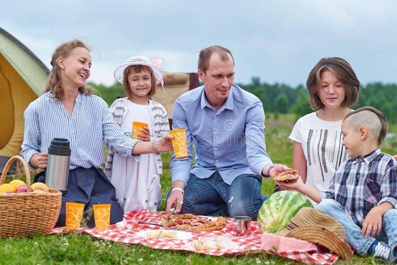 Famille heureuse ayant le pique-nique dans le pr? un jour ensoleill? Famille appr?ciant des vacances de camping dans la campagne image libre de droits