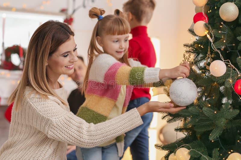 Famille heureuse décorant l'arbre de Noël dans la chambre image libre de droits
