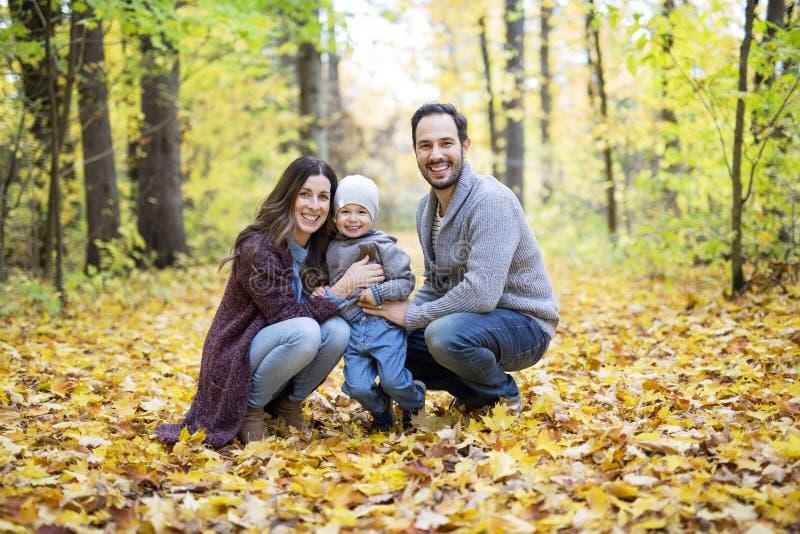 Famille heureuse détendant dehors en parc d'automne photo stock