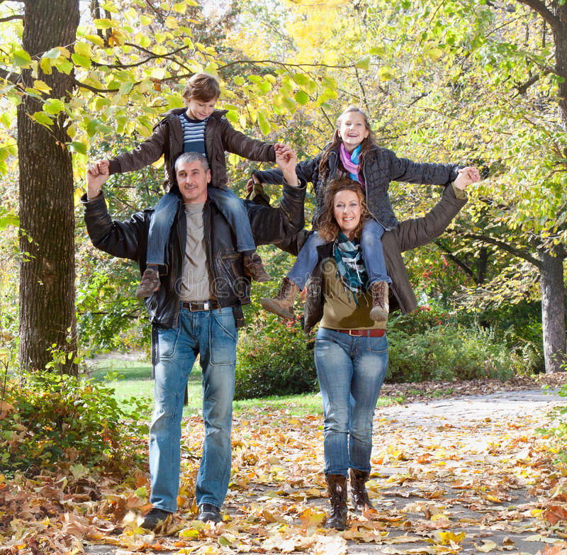 Famille heureuse détendant en parc d'automne image libre de droits