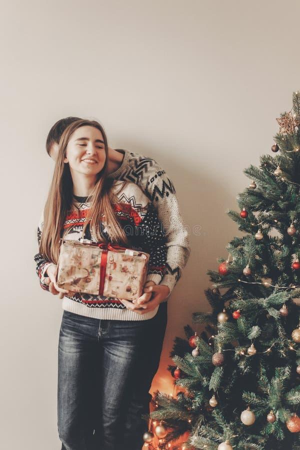 Famille heureuse dans des chandails élégants échangeant des cadeaux dans le roo de fête images stock
