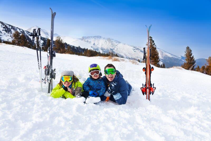 Famille heureuse dans des masques de ski s'étendant sur la neige photo stock
