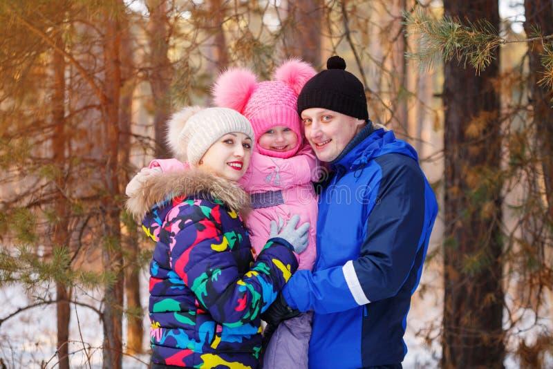 Famille heureuse dans la forêt d'hiver passant le temps extérieur en hiver photo stock