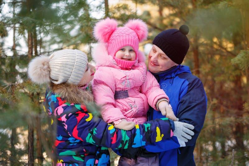 Famille heureuse dans la forêt d'hiver passant le temps extérieur en hiver images stock