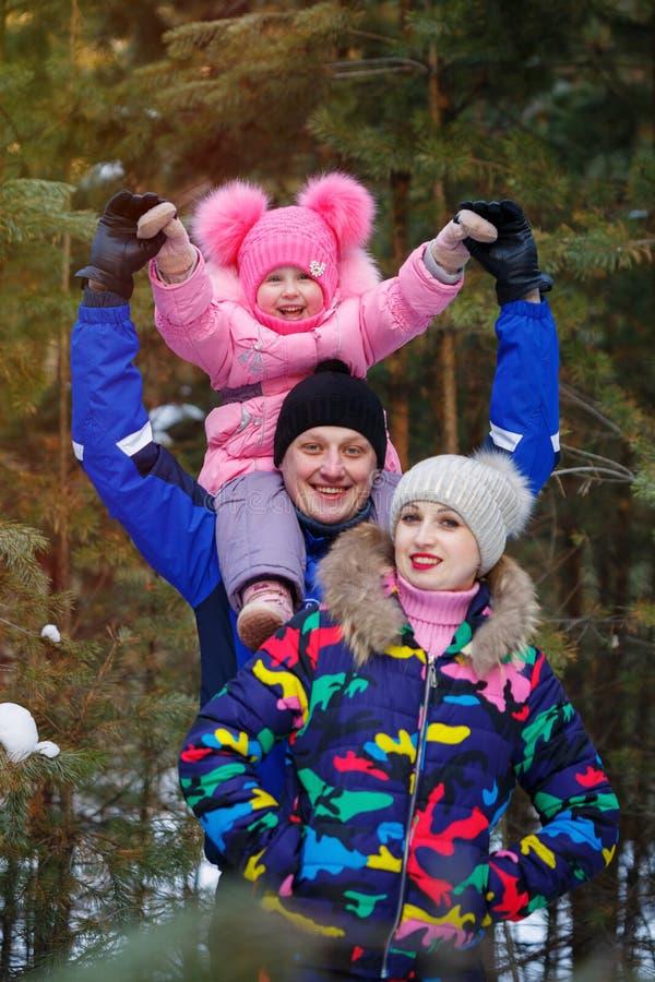 Famille heureuse dans la forêt d'hiver passant le temps extérieur en hiver photos stock