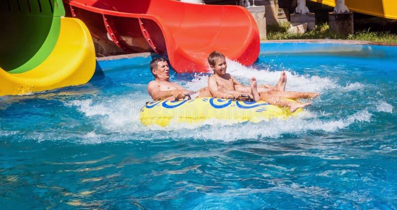 Famille heureuse de deux après glissière de parc aquatique photographie stock libre de droits