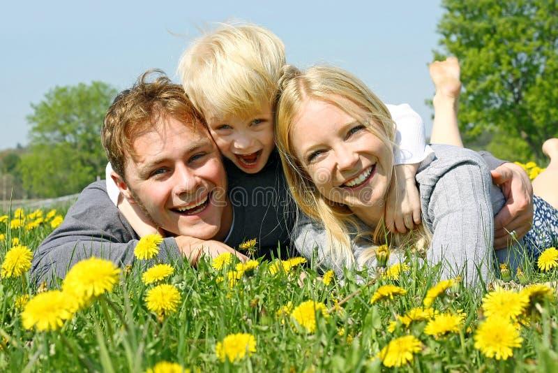 Famille heureuse de trois personnes détendant dans le pré de fleur photos stock