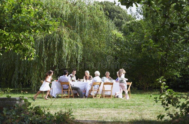 Famille heureuse dinant ensemble dans le jardin photo stock